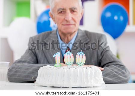 Senior man with cake on  one hundredth birthday - stock photo
