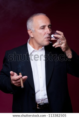 senior man with cigar drinking alcohol from glass over red background