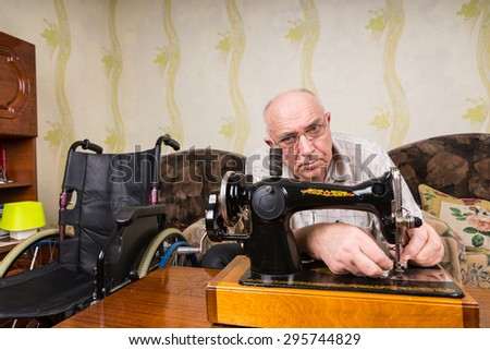 Senior man with disability wearing eyeglasses while using a vintage mechanical sewing machine at home, on a wooden table, near a sofa and a wheelchair - stock photo