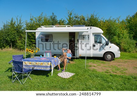 Senior man with dog and mobil home at campground - stock photo