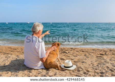 Senior man with dog in white suit sitting at the beach  - stock photo