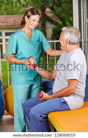 Senior man with dumbbells at physiotherapy with physiotherapist - stock photo