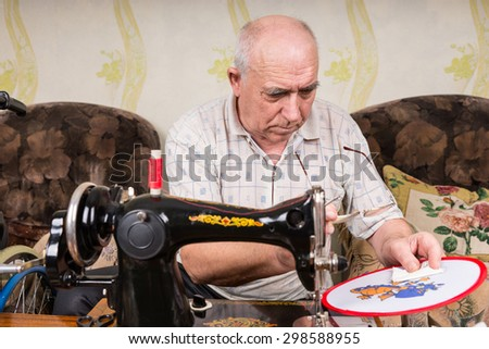 Senior Man with Eyeglasses Inspecting Needle Point Stitches on Craft Wall Hanging Completed Using Old Fashioned Manual Sewing Machine in Living Room at Home - stock photo