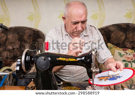 Senior Man with Eyeglasses Inspecting Needle Point Work on Wall Hanging Using Old Fashioned Manual Sewing Machine at Home in Living Room - stock photo
