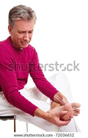 Senior man with foot pain massaging his feet - stock photo
