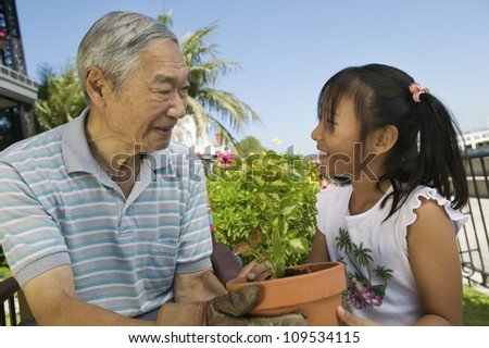 Senior man with granddaughter working in the garden - stock photo