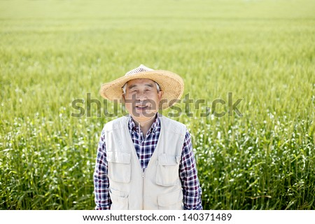 Senior man with hat in farmland - stock photo