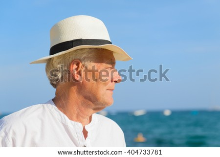 Senior man with hat portrait at the beach - stock photo