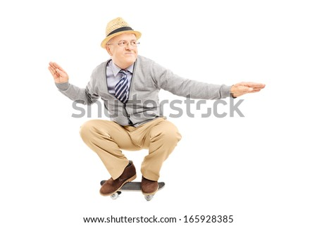 Senior man with hat riding a skateboard isolated on a white background - stock photo