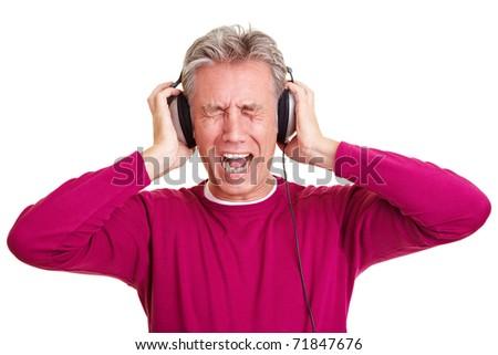 Senior man with headphones on screaming loudly - stock photo