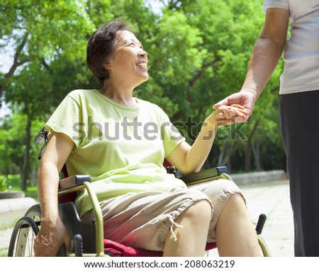 senior man with her disabled wife on wheelchair - stock photo