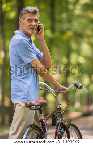 Senior man with his bicycle is talking by phone in park.