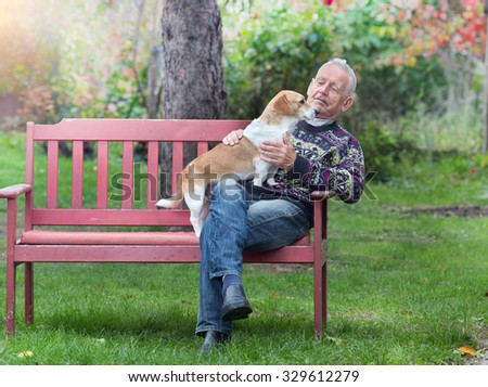 Senior man with his dog sitting on bench in the park - stock photo