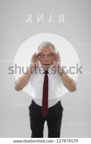 Senior man with his face pressed up against a clear circle in the frosted door of a bank peering in with his hands raised to his eyes trying to attract attention to gain entry or watching in disbelief - stock photo