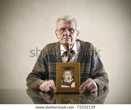 senior man with his picture as a child - stock photo