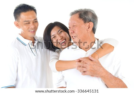 Senior man with his son and daughter. Happy Asian family senior father and adults offspring having fun time at indoor studio. - stock photo