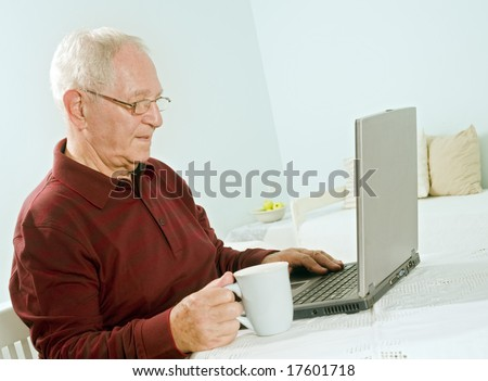 senior man with laptop computer at home - stock photo