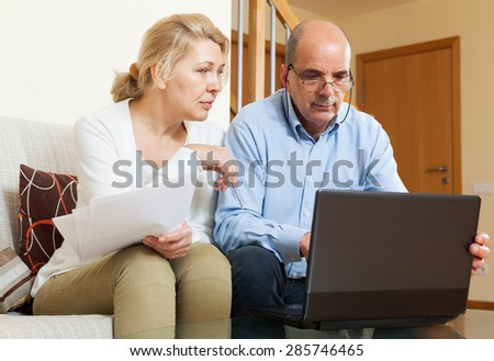 Senior man with mature wife reading business documents and using laptop in home interior - stock photo