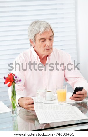 Senior man with newspaper and cell phone at breakfast table