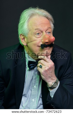 Senior man with party nose and moustache in suit. Funny. Weird. Serious.Studio portrait. - stock photo