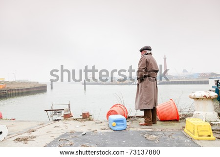 Senior man with raincoat and hat standing in dock. Lonely. Lost. - stock photo