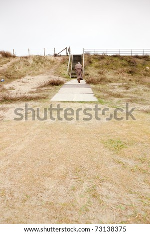Senior man with raincoat and hat walking on stairs outdoors. Cloudy day. Lonely. Lost. - stock photo