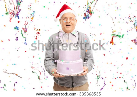 Senior man with Santa hat holding a cake with a bunch of confetti streamers flying around him isolated on white background - stock photo