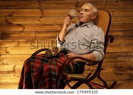 Senior Man With Smoking Pipe Sitting On Rocking Chair In