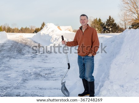 Senior man with snow shovel looking content after removing snow drifts on driveway by digging out from the blizzard