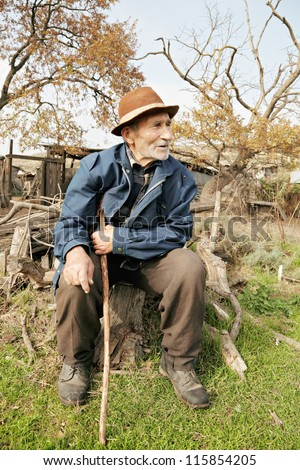 Senior man with stick sitting on stump outdoors - stock photo