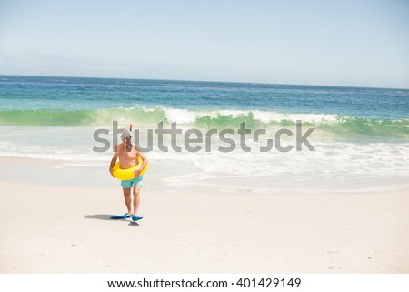 Senior man with swimming ring and flippers on a sunny day - stock photo