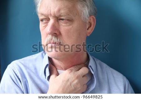 senior man with throat or neck irritation - stock photo