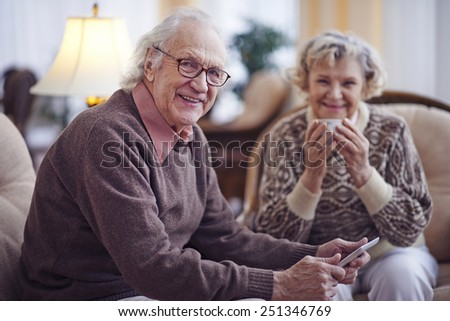 Senior man with touchpad looking at camera with his wife sitting on background - stock photo