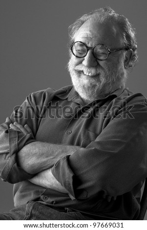 Senior man with white beard and round glasses leans back and laughs. Low key monochrome, vertical layout with copy space. - stock photo