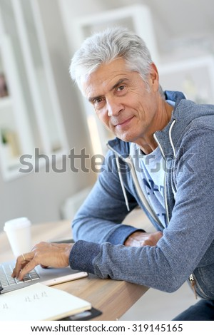 Senior man working from home on laptop computer