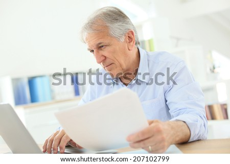 Senior man working on laptop computer - stock photo