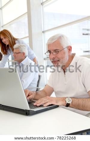 Senior man working on laptop computer - stock photo