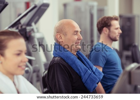 Senior man working out in a gym flanked by a young man and woman with focus to the older man in a health and fitness concept