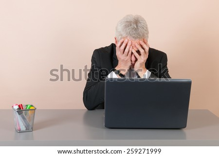 Senior man worried while working with laptop at the office - stock photo