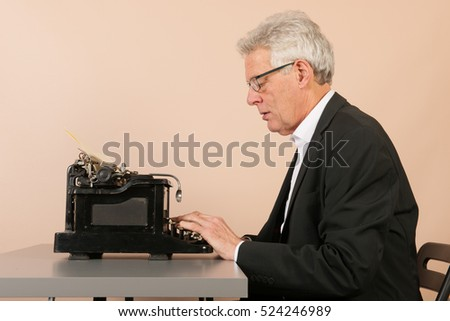Senior man writing with Antique black typewriter