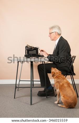 Senior man writing with Antique black typewriter and dog - stock photo