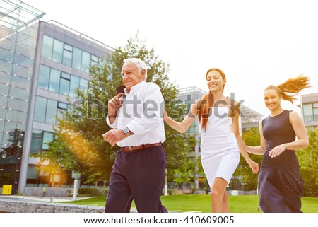 Senior manager and business women running behind each other outdoors - stock photo