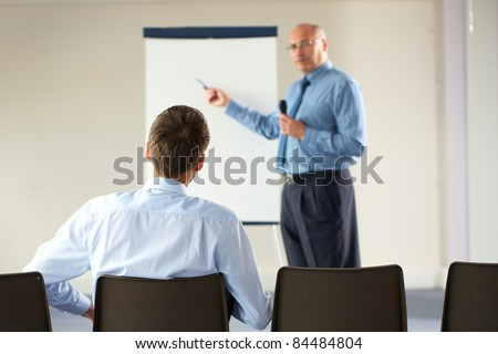 senior manager during seminar, presentation, point to white board and hold microphone, indoor shoot - stock photo