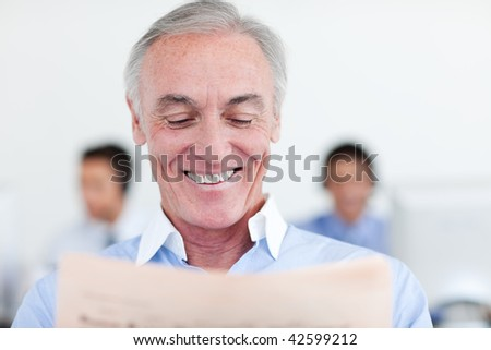 Senior manager reading at his desk in the office - stock photo