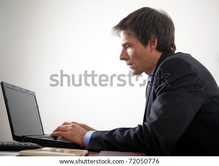 Senior manager working at his laptop in the office - stock photo