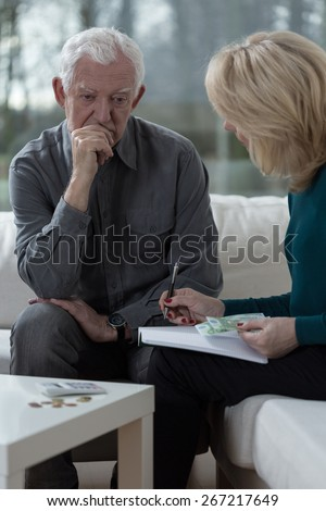 Senior marriage sitting on the sofa and analyzing home budget - stock photo