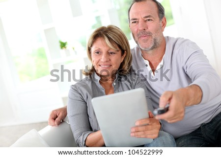 Senior married couple choosing movie on tv - stock photo
