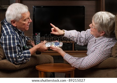 Senior married couple sits in front of television in arguing over who gets to have the remote control. Horizontal format with copy space. - stock photo