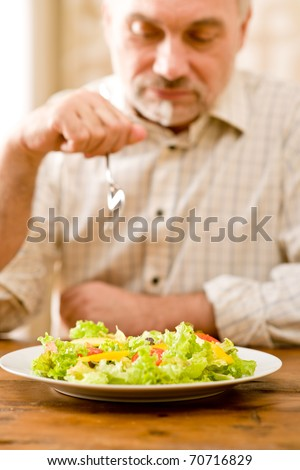 Senior mature man eat vegetable salad at wooden table