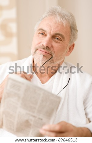 Senior mature man thoughtful read newspaper holding glasses
